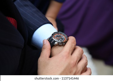 Close up view of groom's hands in a suit adjusting wristwatch, wedding preparations, groom accessories