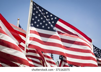 Close up view of a group of American flags waving in the wind against a blue sky background.