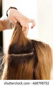 Close up view of hairdresser hand holding strand of hair preparing to cutting and dyeing hair. Haircare, making new hairdo, keratin restoration and hair therapy concept