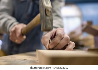 Close up view of hammering a nail into wooden board