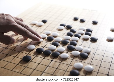 Close up view of hand playing black and white of Chinese go game board.