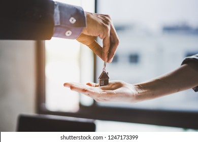 close up view hand of property realtor / landlord giving key house to buyer / tenant.
