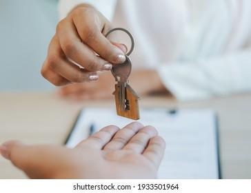 Nahaufnahme Hand von Immobilien Immobilien Vermieter geben Schlüsselhaus an Käufer Mieter.