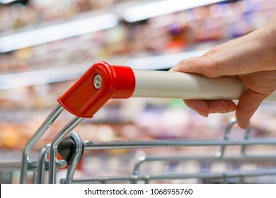 Close up view of a hand with pushcart in supermarket. The racks with the consumer goods in blur. Shallow depth of field