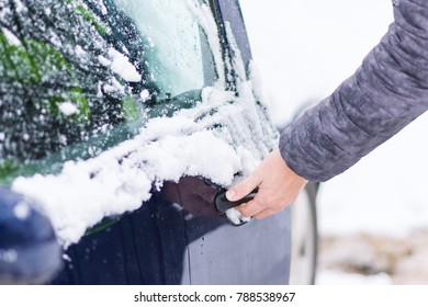 Close up view of hand unlocking frozen car lock at cold winter day.