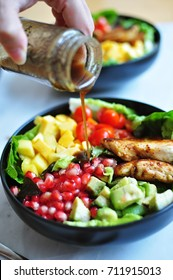 Close up view of hand of woman pouring salad dressing into salad bowl with mango, pomegranate, grilled chicken, tomato, avocado and vegetable