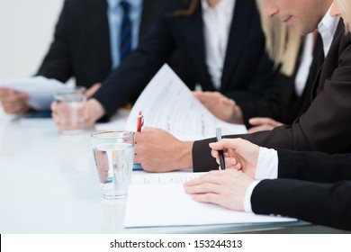 Close up view of the hands of business people taking notes in a meeting seated at a table