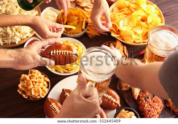 Close up view of hands taking snacks from plates during party