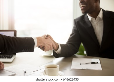 Close up view of handshake between black and white business partners, two smiling multiracial businessmen in formal wear shaking hands over office desk after effective negotiations, signing contract