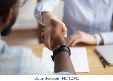 Close up view handshaking male and female hands after successful interview. Caucasian businesswoman and african-american candidate showing mutual respect and intention for good working relationships
