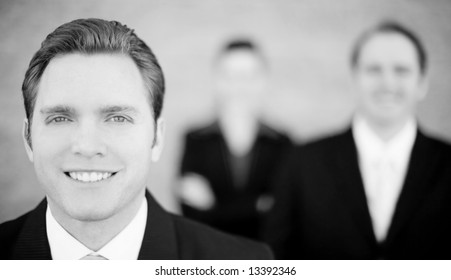 close view of handsome businessman with businesspeople standing in background all looking at camera