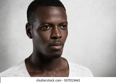 Close up view of handsome dark-skinned male looking serious and thoughtful on blank studio wall background. Young African man with peaceful facial expression and relaxed regular mimics. Horizontal