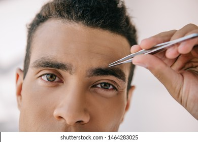 close up view of handsome man plucking eyebrows with tweezer and looking at camera