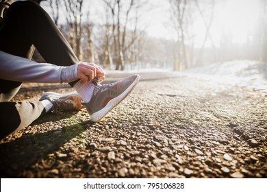 Close up view of hardworking active fitness man hands in winter sportswear tying shoelaces on sneakers while sitting on the road outside in snowy nature.