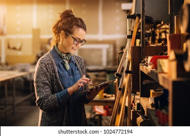 Close up view of hardworking focused professional motivated business woman holding a tablet next to the shelf with tools in the fabric workshop.