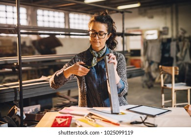 Close up view of hardworking focused professional motivated business woman measuring metal pipe with a tape measure in the sunny fabric workshop.