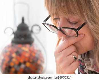Close view head shot.A lady has a thoughtful pose as she looks downwards wearing glasses on end of nose. She has a hand on her face.Vertical.Image