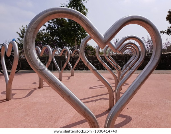 A close up view of the heart shaped bicycle parking racks, located in Greystones town, Ireland. Creative design of a bicycle parking station. Symbol of love for cycling. Sunny summer day.