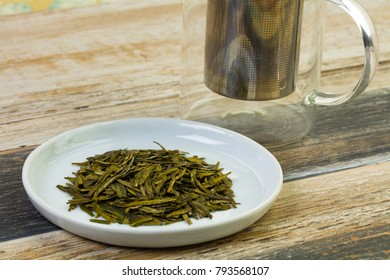 Close up view of a herbal tea blend on a white plate with glass cup on a wood table.