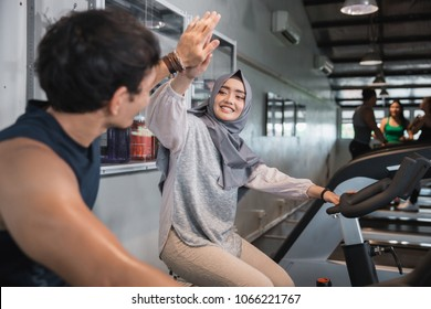 Close up view high five at the gym doing cardio exercises on static bike
