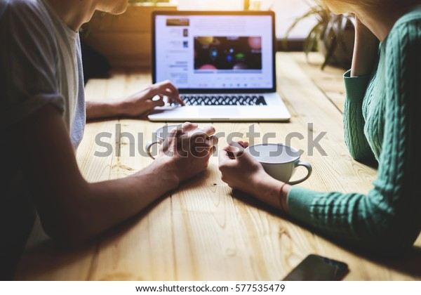 Close up view of hipster friends watching video in social network via portable net-book, while sitting at wooden table in coffee shop. Group of people are reading news information on laptop computer