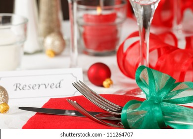 Close up view of a holiday table setting with red and green decorations and placard showing a reserved space