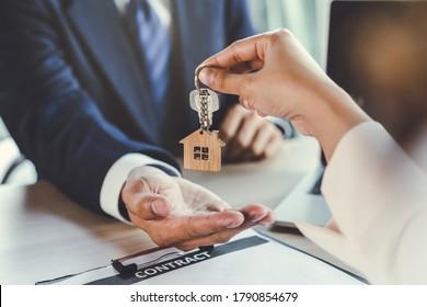Nahaufnahme der Hausschlüssel in der Agent Hand geben, die neue Eigentümer.