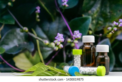 Close view of homeopathic medicine liquid bottles and globule sugar ball pills with wild flower and green leaves background