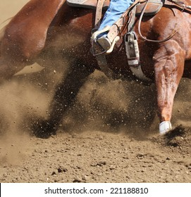 A close up view of a horse sliding in the dirt.