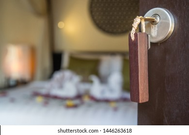 Close up view at hotel room key in the lock, blurred hotel bedroom interior with towel swans and rose flowers on the bed