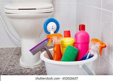 Close Up View Of House Cleaning Products And Tools In White Bucket On Tiled  Floor In