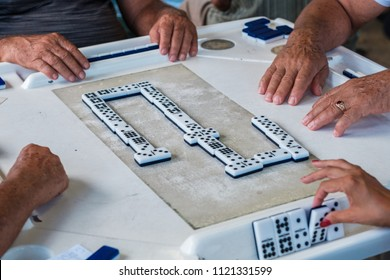 Close up view of individuals playing the domino game in the historic Domino Park in popular Little Havana.