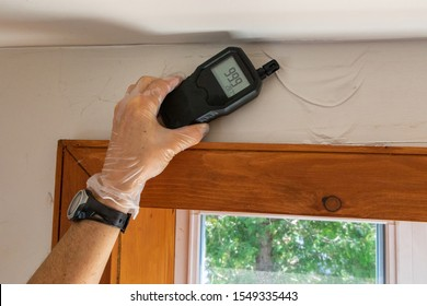 A close up view of an indoor environmental quality assessor using a handheld digital device with lcd numeric display during a residential dwelling check up.