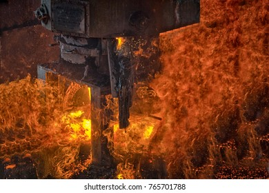 An close view of an industrial furnace being emptied with fire and flames predominant