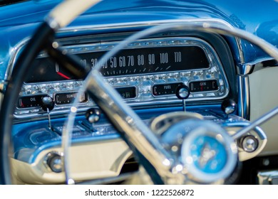 Close up view of inside a vintage car dashboard showing gauges and dash