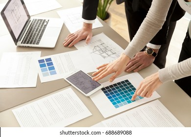 Close up view of Interior designers teamwork with pantone swatch and house building plans on office desk, architects working with blue color palette to choose best paint for home refurbishment