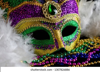 Close up view of a jester mask with a white boa and color coordinating beads.  Conceptual for Mardi Gras, carnival, or festival.