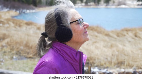 Close view of joyful senior lady observing nature with wind blowing her hair