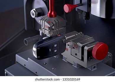 Close view of key copying machine with key. Duplicate machine make new key. Locksmith theme. Blank keys for cutting. Black modern car door opener.