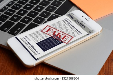 Close up view of keyboard and digital fake News on smartphone. Propaganda and disinformation online. Media and digital concept. All screen graphics are made up by us