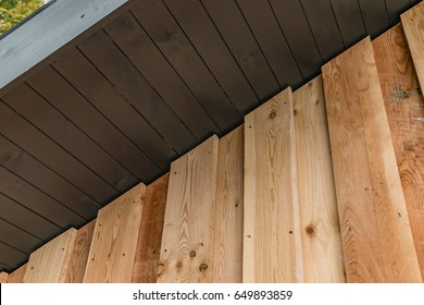 Close up view of larch cladding and painted soffit boards fixed to a residential building in Scotland.