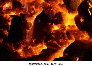 Up close view of a large ceremonial fire made with oak logs is used to heat river stones for sweat lodge.