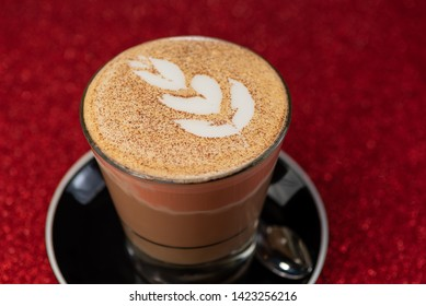 A close up view of a latte art flower on top of a coffee in a drinking glass against a red sparkling background