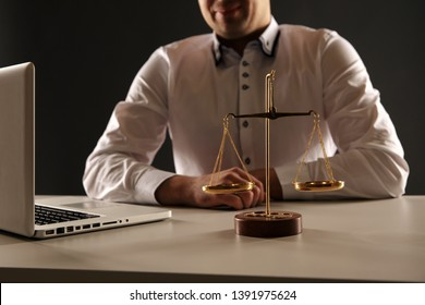 Close up view of lawer man working on a laptop. Libra and Statue of Justice.