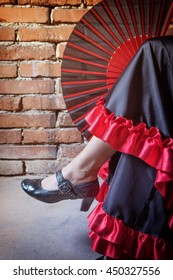 Close up view of leg of woman sitting on a chair and dressed in costume of Flamenco dancer with an open red and black fan. The photo has deliberately darkened edges. Vertically.