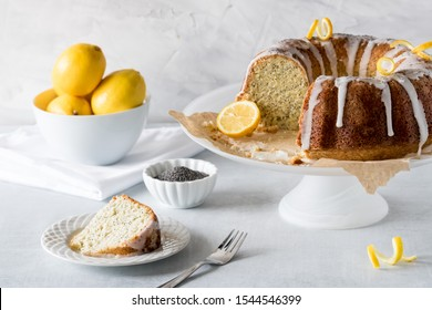 A close up view of a lemon poppyseed bundt cake with a slice of cake in front and a bowl of lemons in behind.