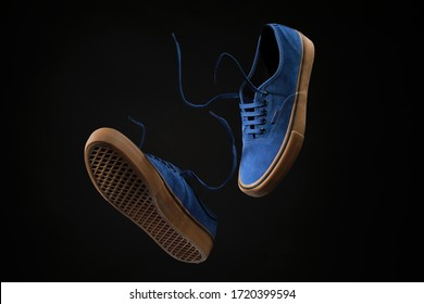 Close up view of levitation blue sneakers shoes with  flying laces over black  background with copy space for text.