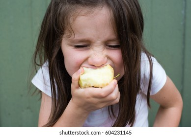 Close up view of little girl taking big bite out of apple (selective focus)