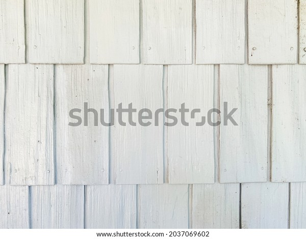 close up view looking at white shingles siding on boathouse barn or house
