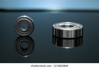 Close up view with low light. Spare part is bearing placed on black glass floor. There is reflection.